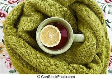 Cup of tea in warm scarf
