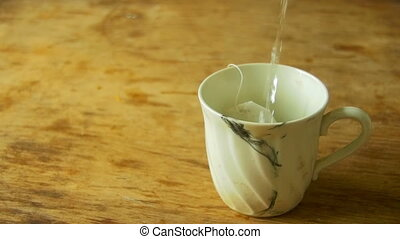 Cup of Tea is Poured Boiling Water in Slow Motion - Cup of...