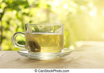 Cup of tea on a blurred background of nature with burst light