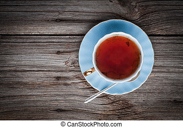 Cup of tea on a wooden background top view with copy space