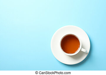Cup of tea on blue background, copy space