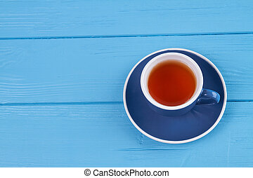 Cup of tea on blue wood.