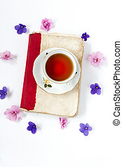cup of tea on book with flower over wite background .