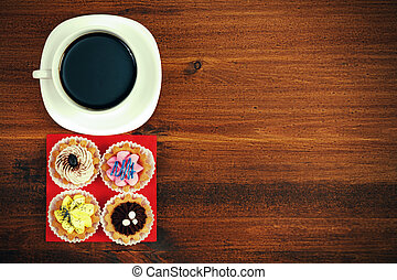 Cup of tea or coffee and four cupcakes on brown table. Top veiw