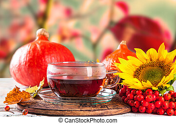 Cup of tea with autumn leaves with season vegetable on...