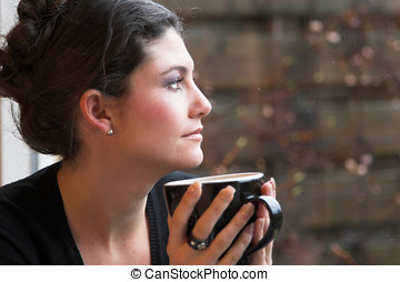 Cup of tea - Pretty brunette staring out of the window and...