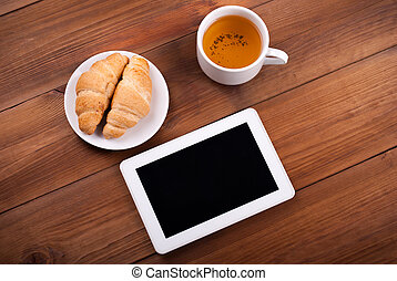 Cup of tea tablet croissants on a wooden table.