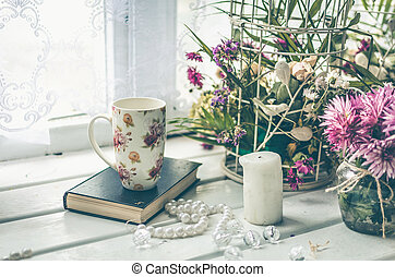 Cup of tea with a book and pink flowers