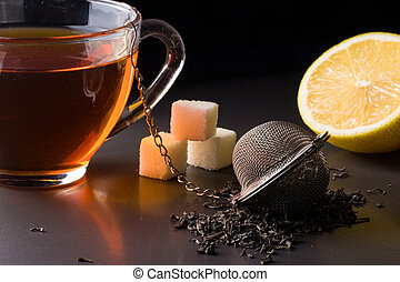 cup of tea with a strainer and lemon on dark background