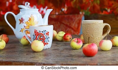 Cup of tea with autumn leaves and apples on wooden table....