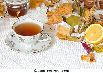 cup of tea with autumn leaves and white napkin on white background.