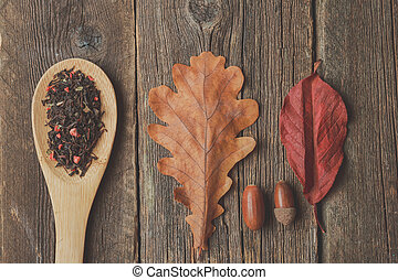 Cup of tea with autumn leaves on wooden background