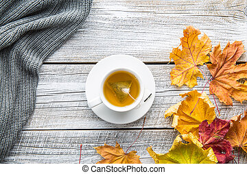 Cup of tea with autumn leaves.