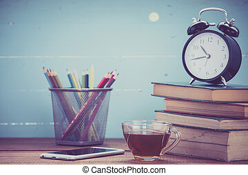 Cup of tea with books and clock on wooden background