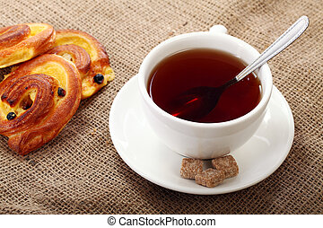 Cup of tea with buns on a tablecloth