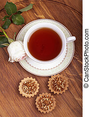 Cup of tea with cake on wood table, view from above