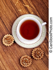 Cup of tea with cakes on a wooden background