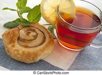 Cup of tea with cinnamon Danish bun