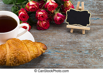 Cup of tea with croissant, fresh roses and blackboard with space for your text  on a wooden background. Perfect image for mother's day