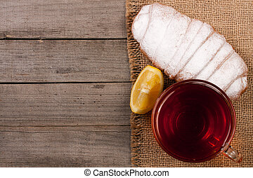 Cup of tea with croissant sprinkled with powdered sugar on old wooden background with copy space for your text. Top view