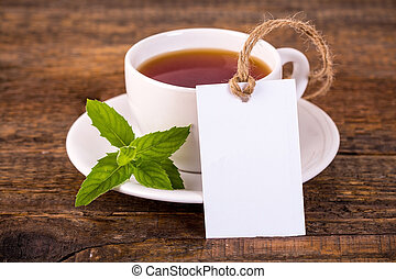 Cup of tea with green leaves and blank tag