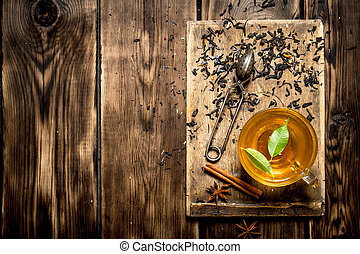 Cup of tea with green leaves.