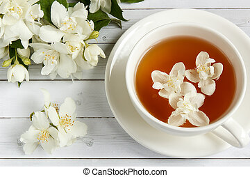 Cup of tea with jasmine flowers on a wooden background