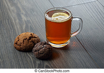 cup of tea with lemon and cookies on a wooden table