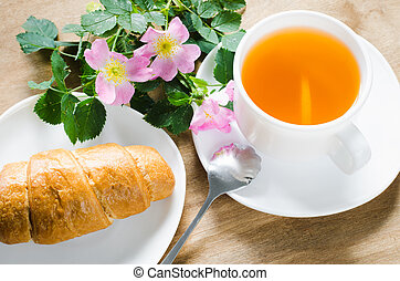 Cup of tea with lemon and croissant.