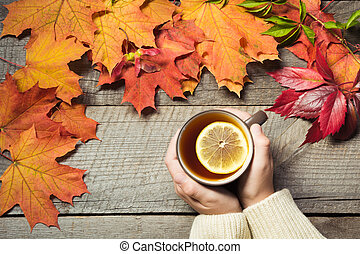 Cup of tea with lemon in hand, colorful autumn leaves on wooden board. Fall still life, vintage. Top view.
