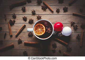 Cup of tea with lemon near cinnamon nad star anise, bulbs