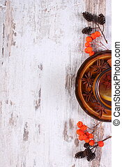 Cup of tea with lemon, spices and autumn decoration on wooden background, copy space for text