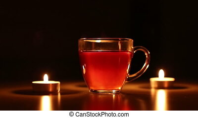 cup of tea with lighting candles