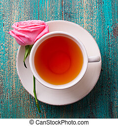 Cup of tea with pink rose. Colorful turquoise wooden background. Close up. Top view.