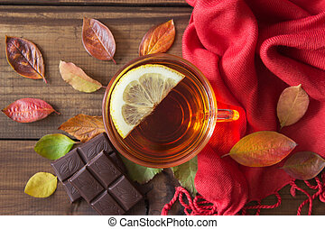 Cup of tea with slice of lemon and chocolate with autumn leaves on old wooden table.