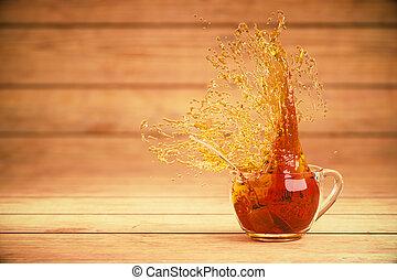 Cup of tea with splash - Splashing cup of tea on wooden...