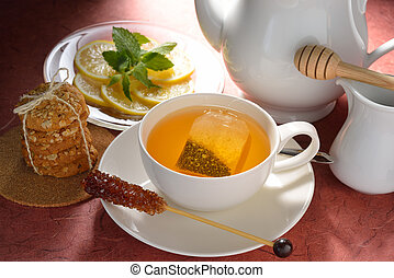 Cup of tea with tea bag and cookies on table
