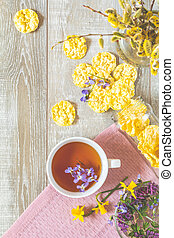 Cup of tea with violet viola, delicious nutritious cereal breads