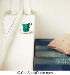 Cup of turquois color on the window sill.