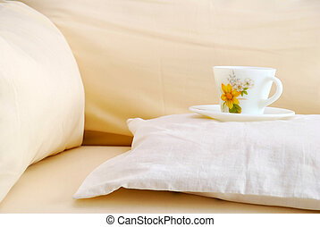 Cup on a cushion on sofa. For relaxation and lifestyle concepts.