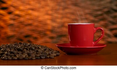 Cup on a red saucer of hot coffee on the aroma spreads room...