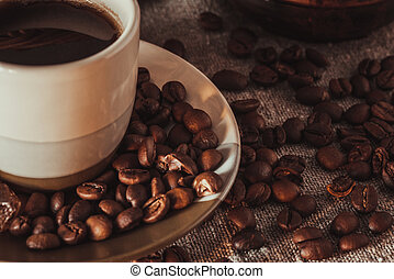 Cup on saucer with scattering of coffee beans and sugar