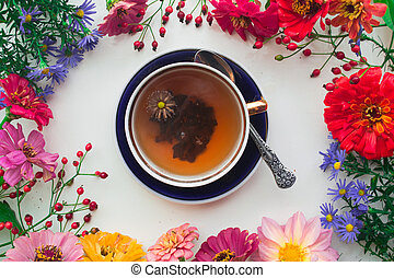 Cup on tea and autumn flowers frame on white background