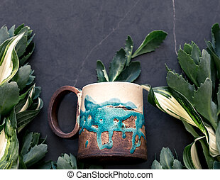 Cup on the background of green leaves
