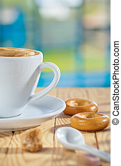 cup spoon sugar and cookie on table