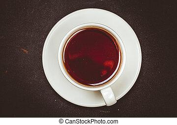 Cup tea on black surface.