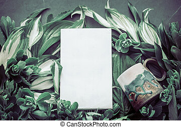 Cup with a book on the background of green leaves