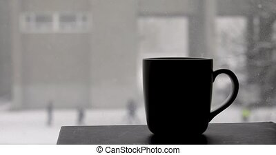 Cup with a hot drink and snow falls - Cup with a hot drink ...