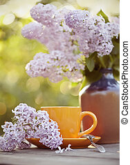 Cup with a spoon and a lilac bouquet in a vase