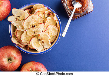 Cup with apple chips, fresh apples and glass jar of apple jam and metallic spoon on blue background.